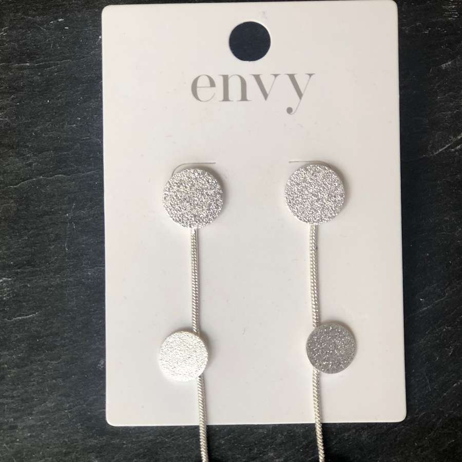 Long silver earrings with textured coin detail