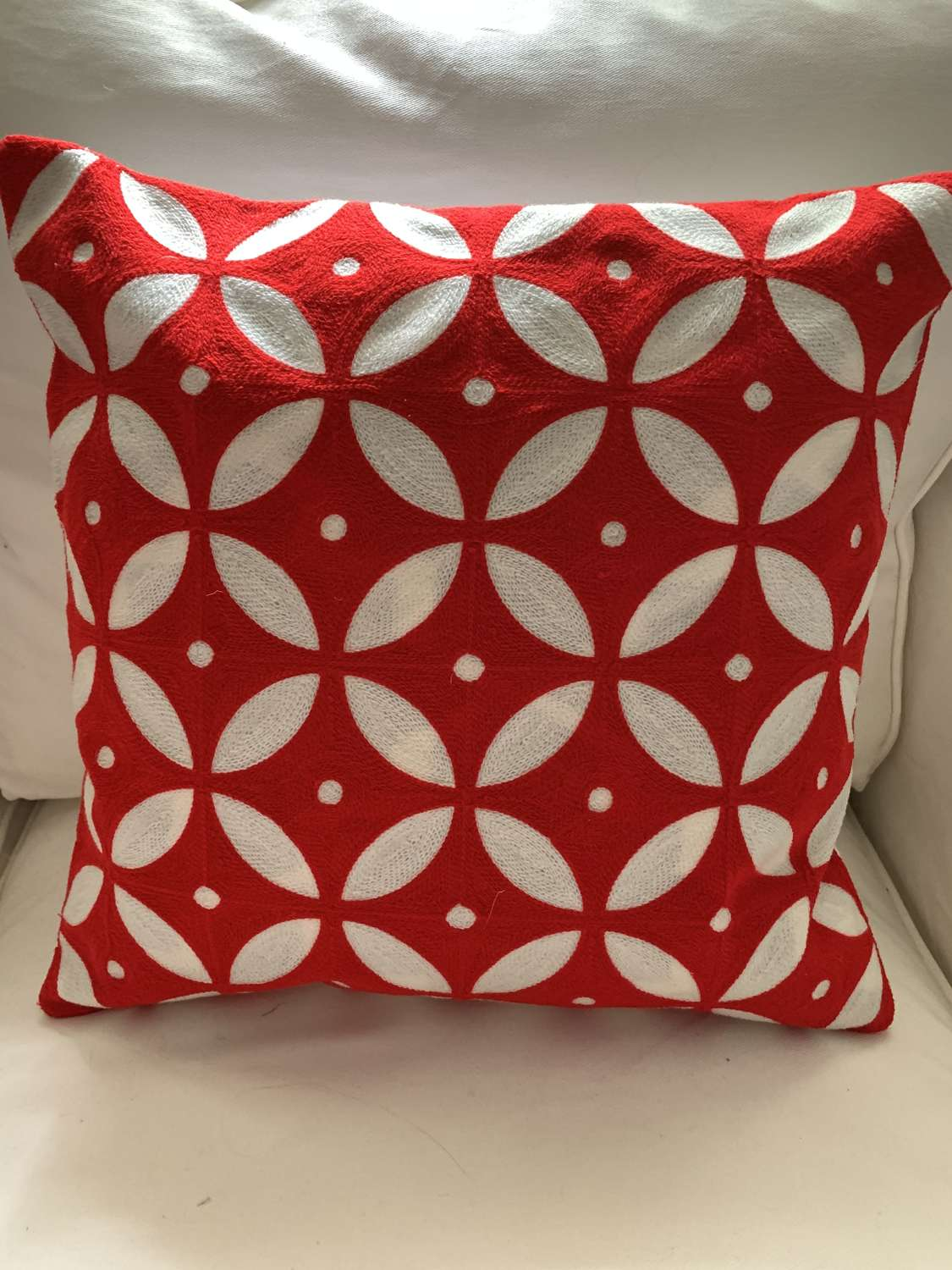 Red crewel work cushion with feather pad